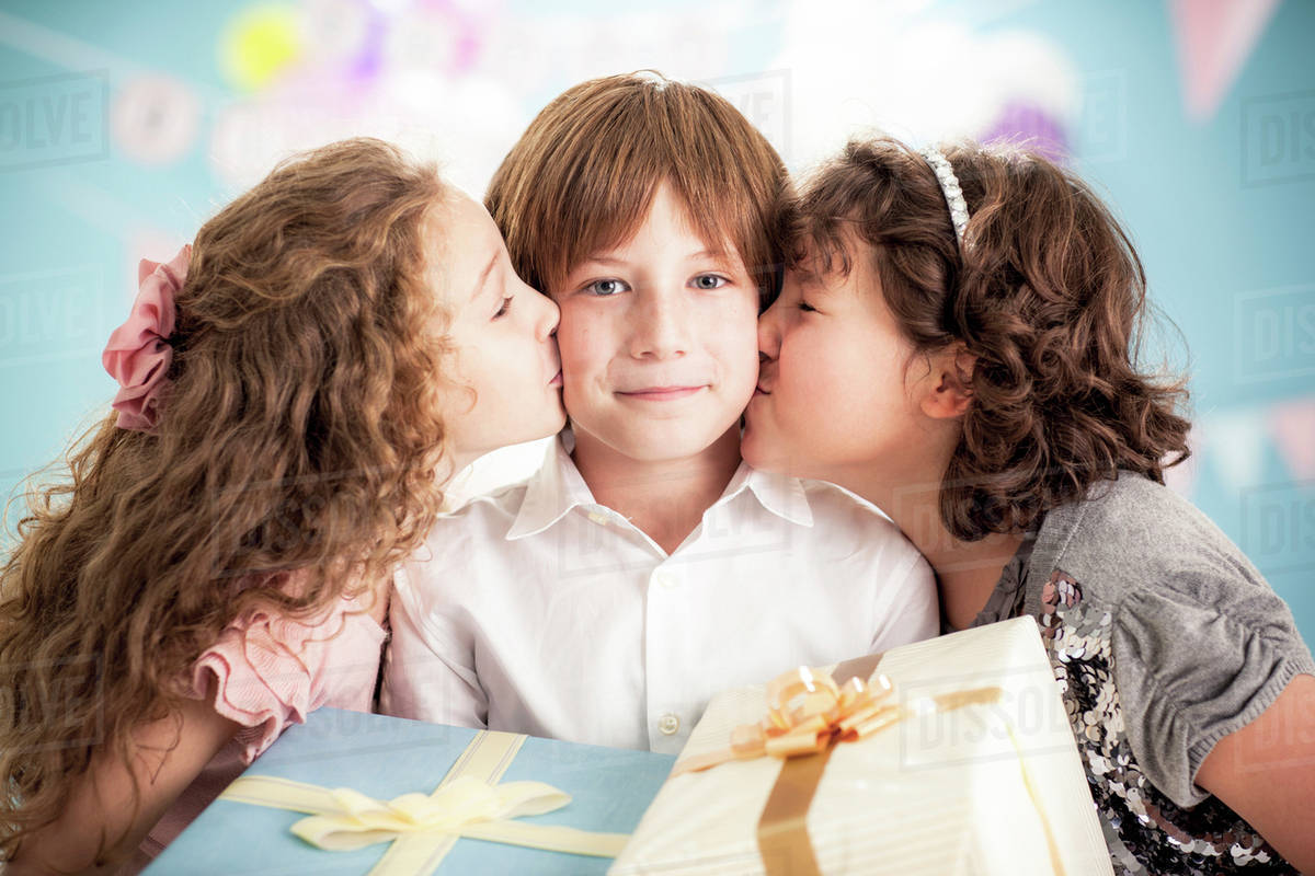 Girls Kissing Cheeks Of Boy At Birthday Party - Stock -6215