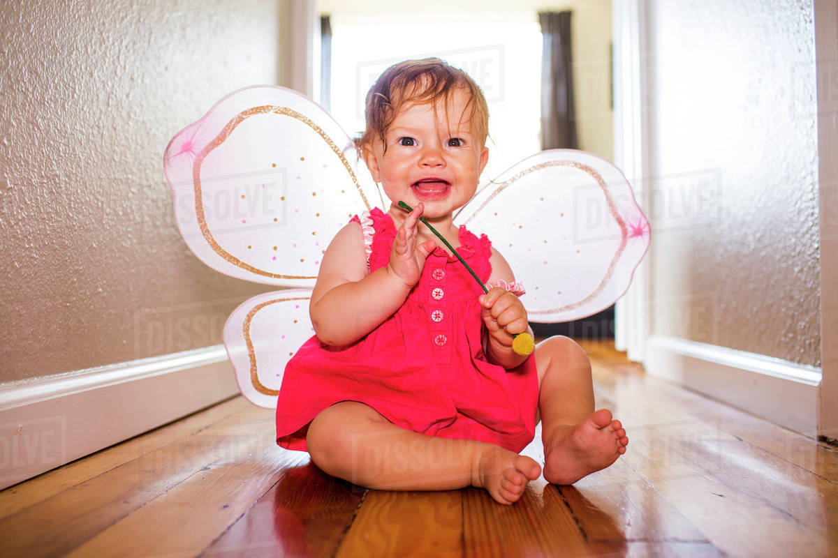 Caucasian baby girl playing in fairy wings Royalty-free stock photo
