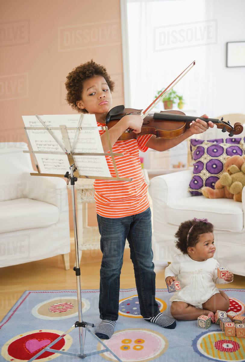 Black boy practicing violin in living room stock photo