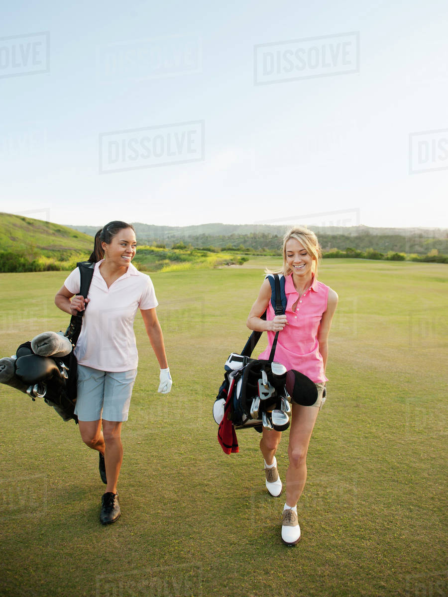 Women Carrying Golf Bags On Course D145 97 929