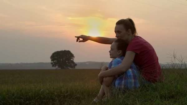 Caucasian mother and daughter looking at crops at dusk Royalty-free stock video