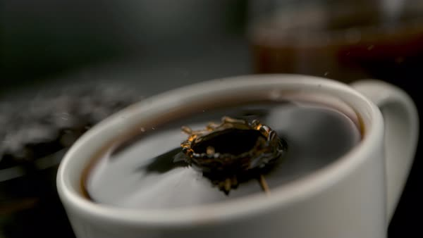Close-up shot of drop falling into a cup of coffee Rights-managed stock video