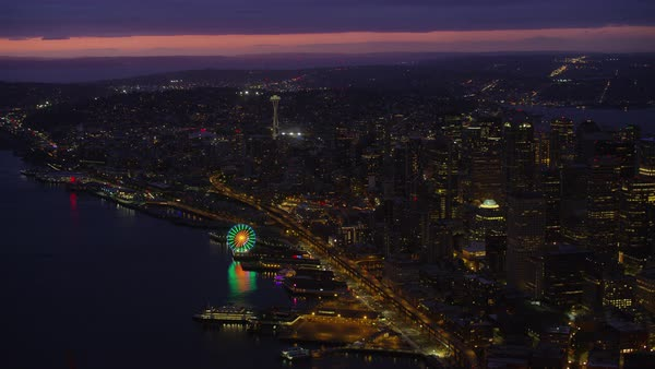 Aerial shot of modern Seattle cityscape with Seattle Great Wheel and Space Needle tower at night, Washington, United States of America Rights-managed stock video