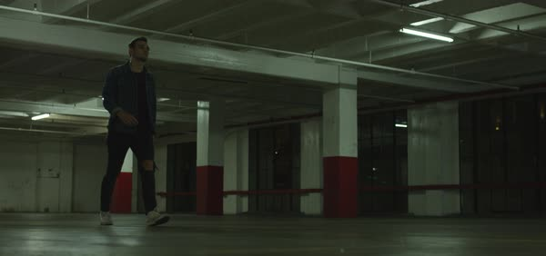 Tracking shot of a man walking in a parking garage Royalty-free stock video