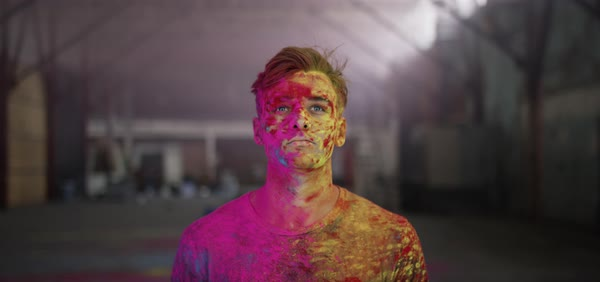 Hand-held shot of a man splashed with colorful powder paint Royalty-free stock video