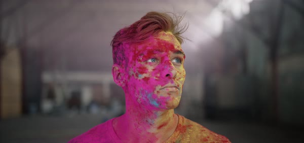 Hand-held shot of a young man splashed with colorful powder paint Royalty-free stock video