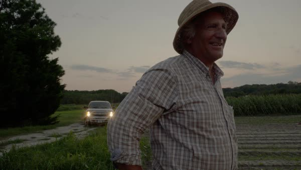 Hand-held shot of a smiling farmer standing on a crop field Royalty-free stock video