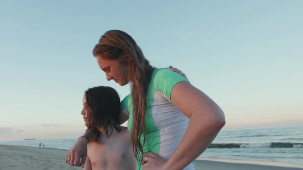 Hand-held shot of a boy and a young woman standing on a beach Royalty-free stock video