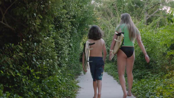 Slow motion shot of a boy and a young woman walking with surfboards Royalty-free stock video