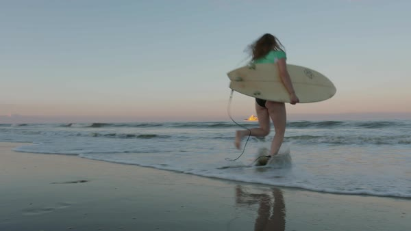 Slow motion shot of a young woman running into sea with a surfboard Royalty-free stock video