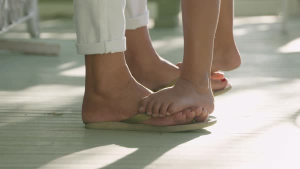Hand-held shot of a girl standing on feet of her mother Royalty-free stock video