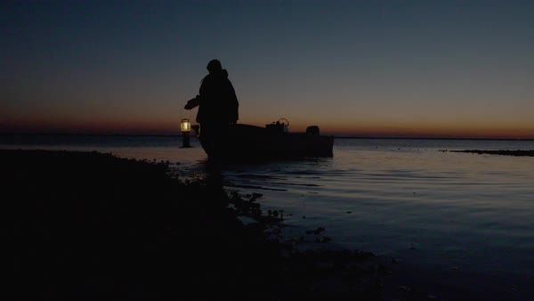 Slow motion shot of fisherman walking away from a boat with a lantern Royalty-free stock video
