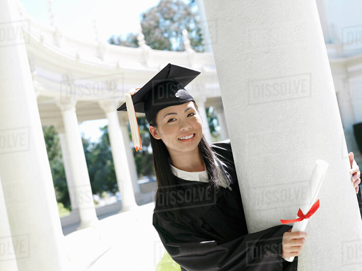 University student in graduation gown and mortar board holding ...