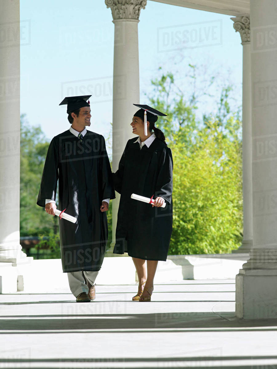 University students in graduation gowns and mortar boards walking in ...