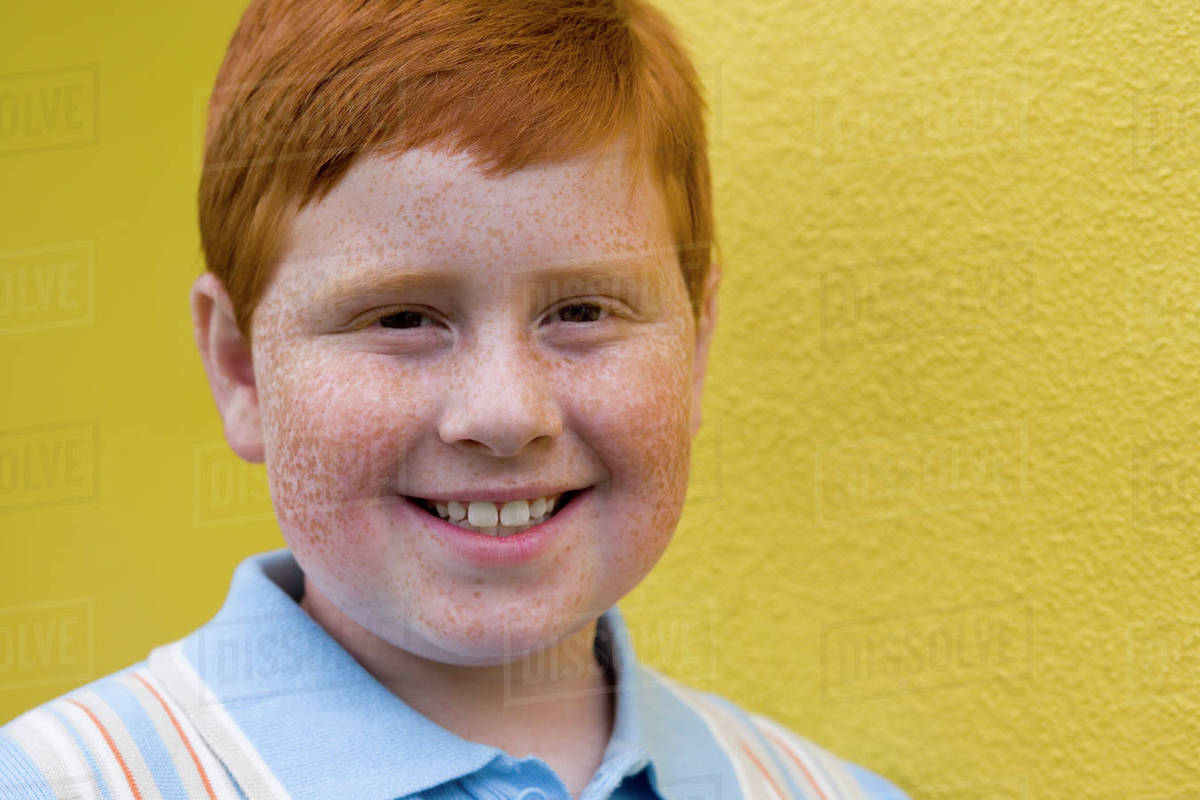 Boy 9 11 with freckles and ginger hair standing beside yellow wall smiling close up portrait