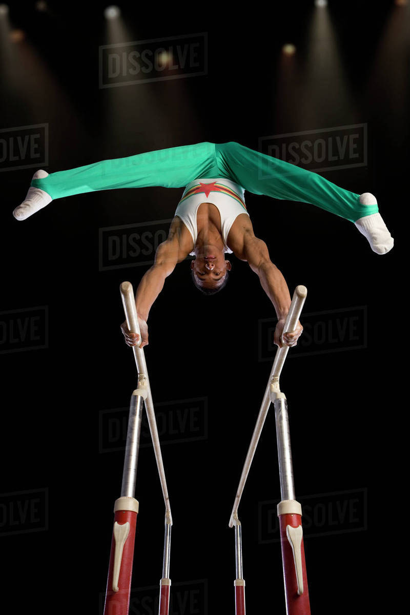 Male gymnast performing on parallel bars, low angle view stock photo