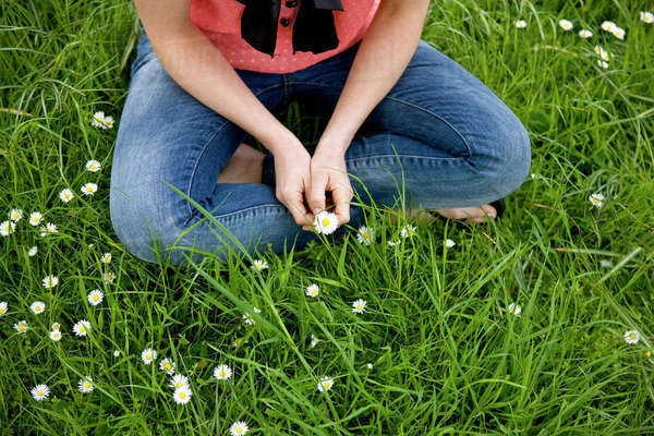 A woman sitting in the grass cross-legged, holding a daisy Royalty-free stock photo