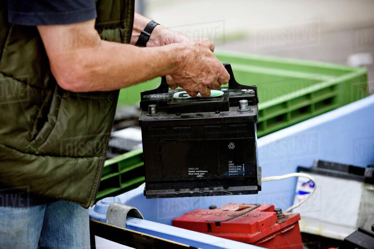 A Senior Man Recycling Car Battery