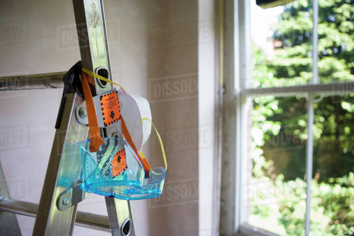Protective safety goggles and dust mask hanging from step ladder in room  beside window stock photo