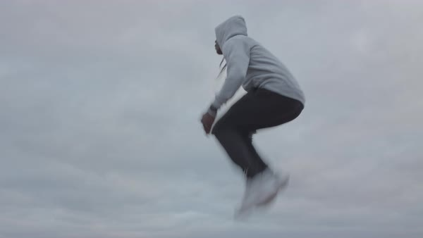 A young man jumping and doing exercise outdoors Royalty-free stock video