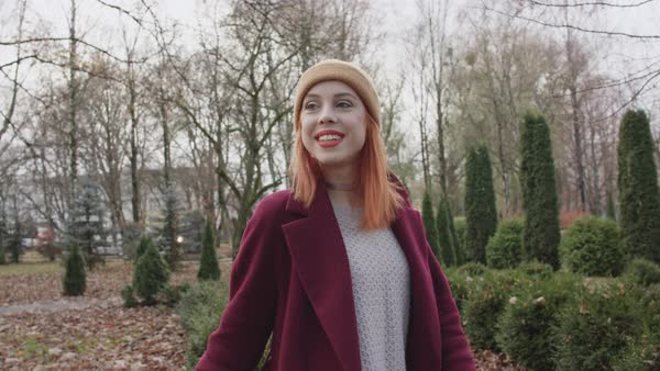 A young woman turning toward camera and smiling while standing in a park Royalty-free stock video