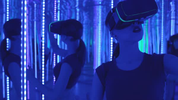 A young woman wearing VR goggles standing in a mirrored room and moving her hands in air Royalty-free stock video
