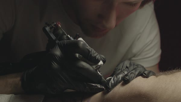 Close-up of a tattoo artist tattooing a man's leg Royalty-free stock video