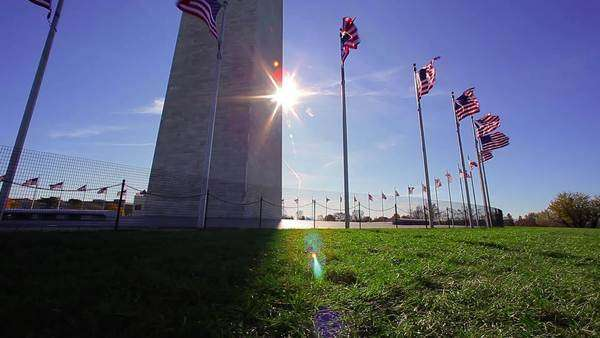 A tracking shot with a lens flare of flags in front of the Washington Monument with the sun behind the monument Royalty-free stock video