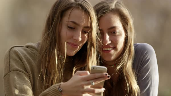 Up close view of teenage girls looking at same smartphone and smiling. Royalty-free stock video