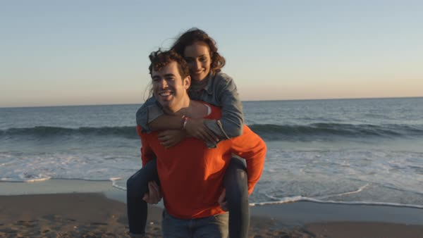 Young couple running to camera on beach, man carrying woman Royalty-free stock video