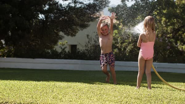 Two children playing with water hose in garden Royalty-free stock video