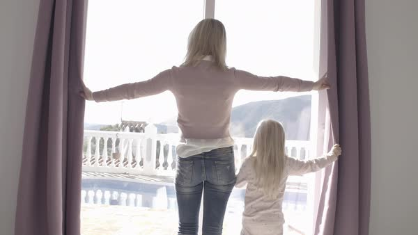 Mother and daughter at home opening curtains in morning Royalty-free stock video