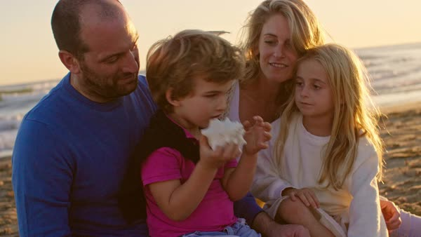 Young family sitting together on beach playing with sea shell Royalty-free stock video