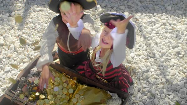 Two children in pirate costumes playing with treasure chest and throwing gold coins in the air Royalty-free stock video
