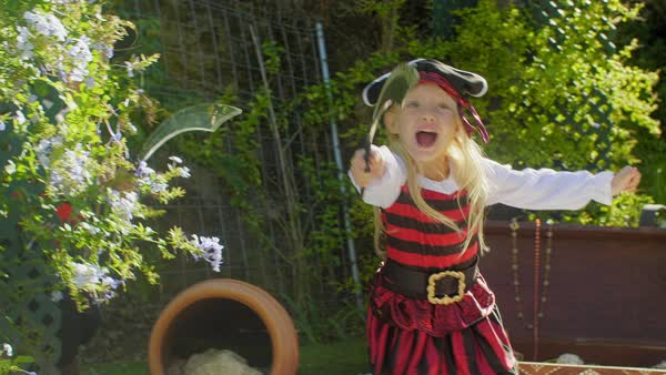 Two children in pirate costumes ambushing from behind tree Royalty-free stock video