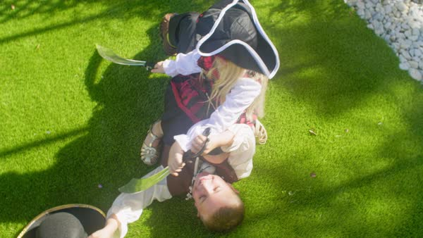Two children in pirate costumes play fighting with toy swords Royalty-free stock video