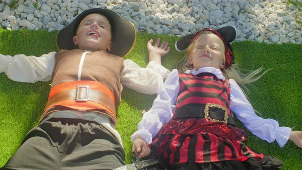 Two children in pirate costumes falling back onto ground playing dead Royalty-free stock video