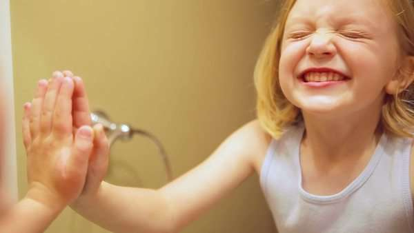A proud adorable little girl looks at her teeth in the mirror. Royalty-free stock video