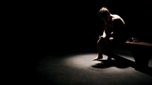 A fighter sits on bench under a light in the dark prepping himself mentally for his fight Royalty-free stock video