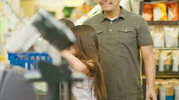 A cute young family goes through a check out line at a grocery store Royalty-free stock video