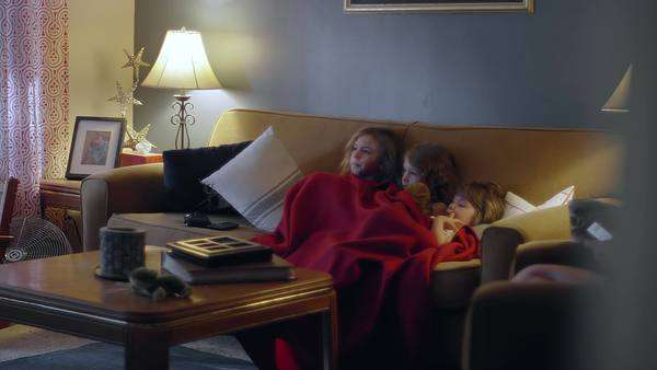 Three sisters sitting on a couch sharing a blanket and watching TV Royalty-free stock video