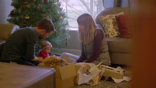 Parents opening presents with their baby in front of the tree on Christmas morning Royalty-free stock video