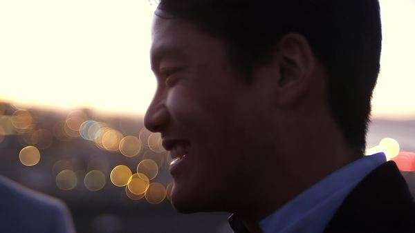 Close up of a man laughing with friends at dusk with some sweet bokeh behind him Royalty-free stock video