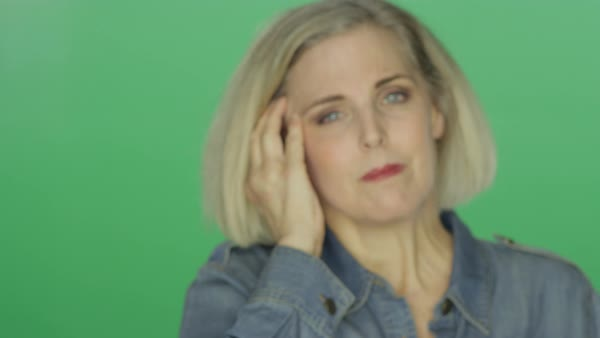 Beautiful older woman suffering a headache and looking worried, on a green screen studio background  Royalty-free stock video