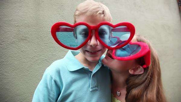 A girl in giant heart sunglasses kisses a boy wearing the same thing Royalty-free stock video