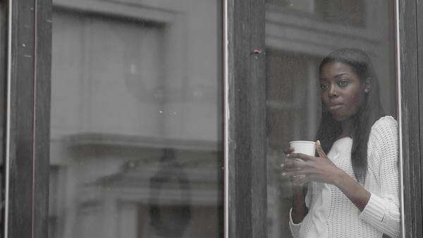 Close up of a woman behind a glass window looking out. A man holding an umbrella walks past Royalty-free stock video