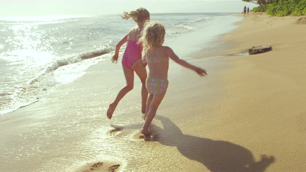A pair of cute sisters run down the beach along the surf together Royalty-free stock video