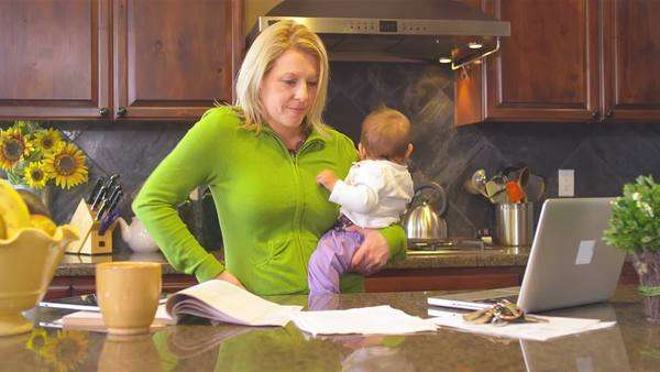 A busy mom tries to multitask with a baby in her arms Royalty-free stock video