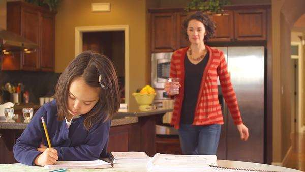 A mother brings her daughter a glass of water, as the girl does homework Royalty-free stock video