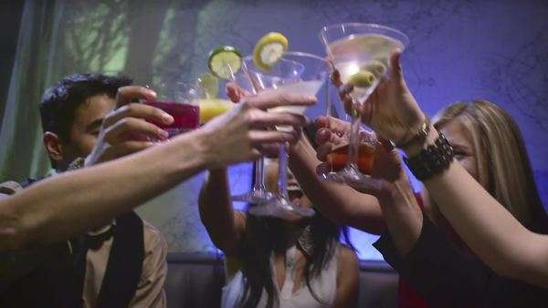 Group of friends sitting at a table in a club cheering there drinks Royalty-free stock video